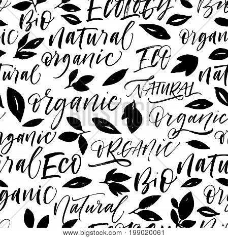 Seamless eco pattern with phrases and leaves. Set of eco phrases : organic natural bio eco. Ink illustration. Hand drawn ornament for wrapping paper.