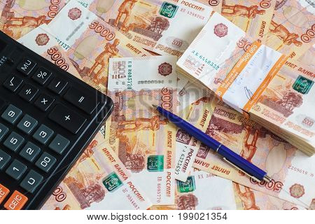 The Concept Of Planning Income And Expenses: Calculator And Ball-point Pen And A Pack Of Half A Mill