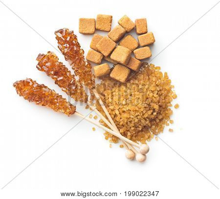 Brown cane sugar, cube sugar and crystalline sugar on wooden sticks isolated on white background. Top view.