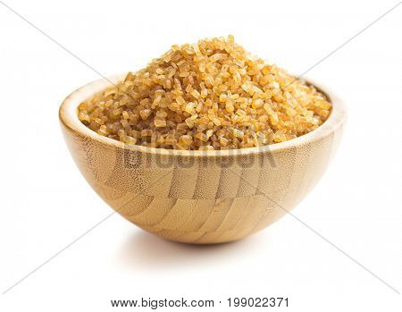 Brown cane sugar isolated on white background. Sweet sugar in bowl.