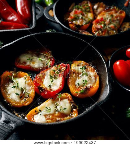 Grilled  peppers  stuffed with cheese and herbs on iron pan on a black background. Delicious and nutritious vegetarian food