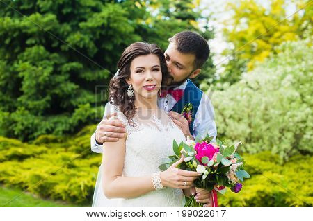 Groom hugs the bride's shoulder outdoors. A man in a red bow tie. Bride in wedding dress with bouquet.