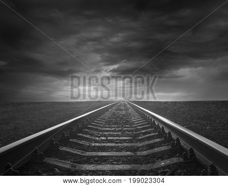 rails going away into the gloomy distance. Black and white image with rails going away into the dark sky landscape