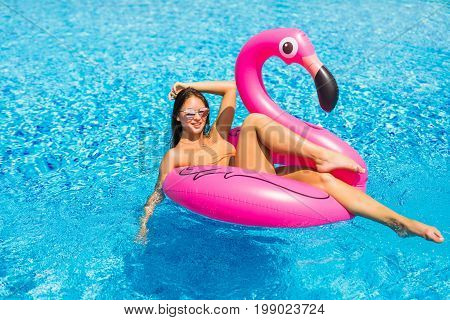 Beautiful Woman, Wearing Swimsuit, Lying On A Pink Flamingo Air Mattress In A Pool Of Blue Water, Su