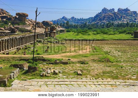 View of ancient ruins of Krishna Bazaar in Hampi, Karnataka, India. Landscape with unique mountain formation with tropical nature hills on the horizon and old hindu temple. UNESCO World Heritage Site