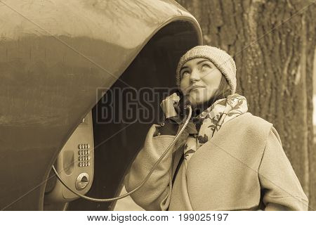 young woman in coat and hat smiling and talking on the red public telephone. Autumn photo of a girl talking on the phone outside in the rain.