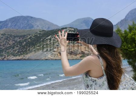 Woman traveler makes a self in the background beautiful natural view mountain on the island. Concept - tourism travel photos from vacation