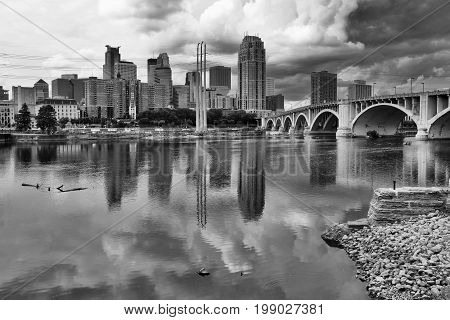 Minneapolis downtown skyline and Third Avenue Bridge above Mississippi river in black and white. Midwest USA Minnesota state.