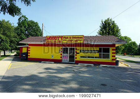 JOLIET, ILLINOIS / UNITED STATES - JULY 17, 2017: The red and yellow cinder block building, which previously housed Moody's Fish and Chicken restaurant, is for sale or lease.