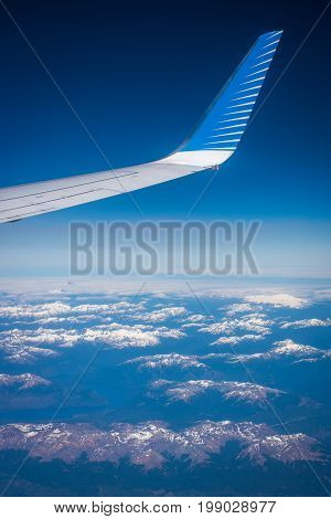 View of the wing tip of the aircraft. Wing of an airplane against a background in the sky. A view of the wing of an airplane on the background of the earth.