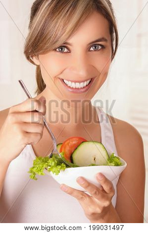 Beautiful young woman wearing a white t-shirt and holding in her hand a healthy salad.