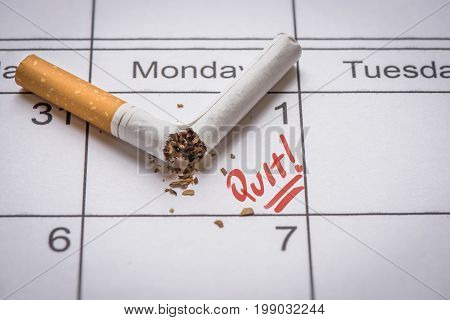 Broken cigarette on calendar. Time to quit smoking concept