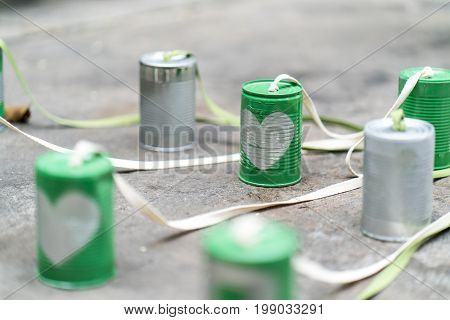 Silver heart on green cans connected with rope on cement floor. Cans attached with big bike for bride and groom riding together for new chapter of life. Just married sign.