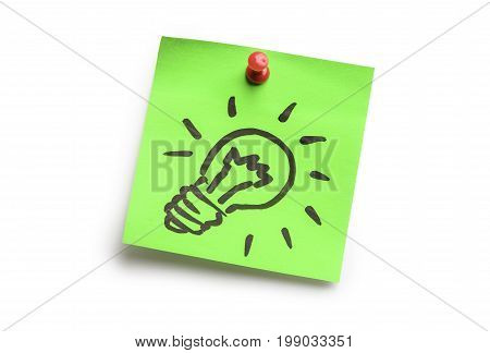 Light bulb on green adhesive notes isolated on white background. Idea concept