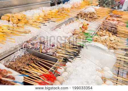 Meat and sea food satay sticks on ice ready for selection and cooking on a street food stall.
