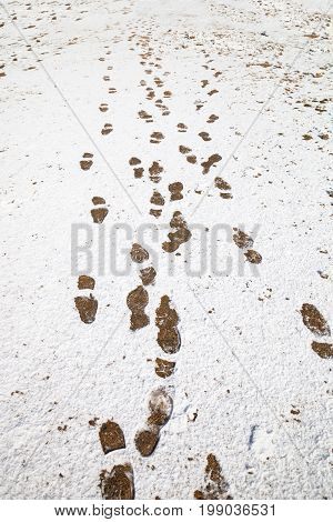winter background with foot steps on snow ground.