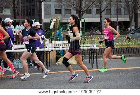 NAGOYA JAPAN - MARCH 13, 2016: Nagoya Women's Marathon 2016. Women's running in the downtown. in motion blur. Course Start and finish at Nagoya Dome Distance 42.195km. Nagoya city Japan.