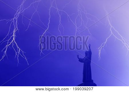 Lightning flashes over the statue of worshiper concept of religion