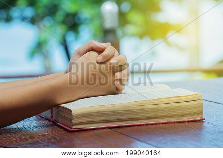 The praying hands on the table Belief in one God devotional Bible Pious  Easter Forgive scriptures read