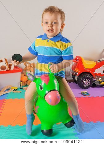 The little happy boy jumping toy horse.