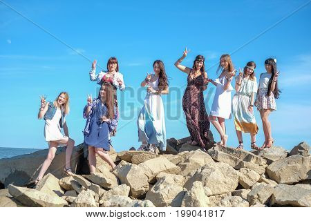 Group of young womens standing together at a beach on a summer day. Happy young girls enjoying a day at beach.