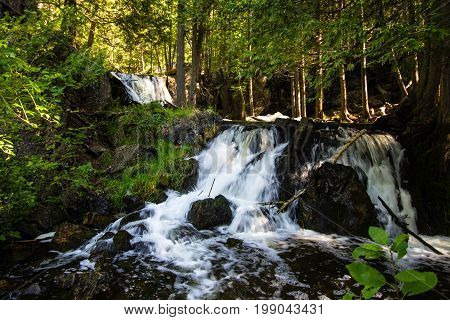 Upper Peninsula Michigan Roadside Waterfall. Fumee Falls is a beautiful waterfall located in a roadside park along US-2 in Dickinson County in the Upper Peninsula of Michigan.
