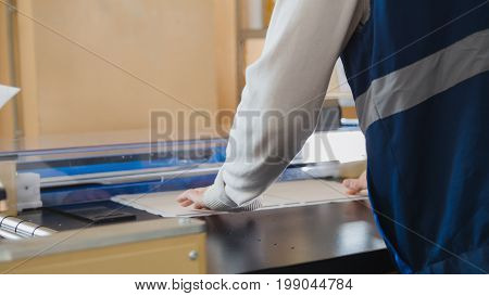The printing house employee is working on printing at the machine, in a printing factory