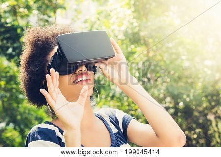 Afro woman enjoying watching 3D simulation video from virtual reality (VR) headset - people and technology concept