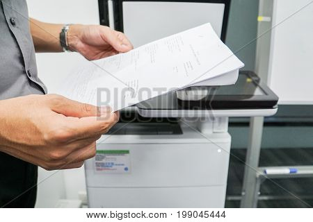 businessman hold paper for scanning on the office printer