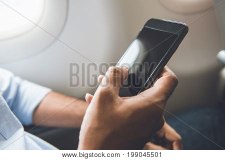 Male passenger just turned off mobile phone on the airplane while traveling for safe flight