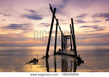 Old wooden bridge wreck on beach at Phang-nga Thailand.