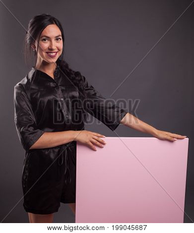 Young confident woman portrait of a confident businesswoman showing presentation, pointing placard black background. Ideal for banners, registration forms, presentation, landings, presenting concept.