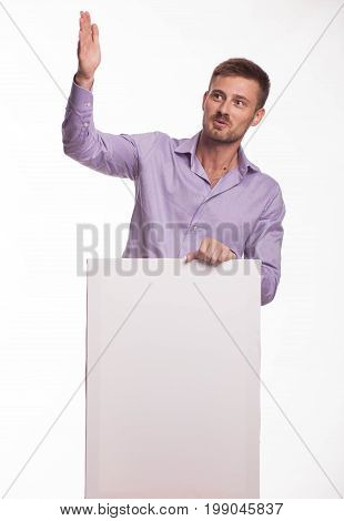 Young playful man portrait of a confident businessman showing presentation, pointing paper placard gray background. Ideal for banners, registration forms, presentation, landings, presenting concept.