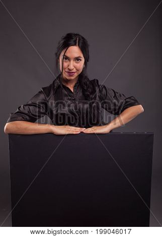 Young sexy woman portrait of a confident businesswoman showing presentation, pointing placard black background. Ideal for banners, registration forms, presentation, landings, presenting concept.