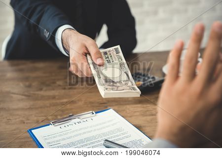 Businessman rejecting money Japenese yen banknotes offered by his partner while making contract - anti bribery concept