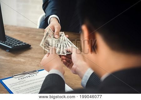 Businessman giving money Japanese yen currency to his partner while making contract