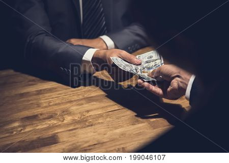 Dishonest businessman secretly giving money to his partner in the dark - bribery scam and venality concepts