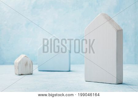 Model of a wooden house on blue background. Construction, real estate, insure, home, building, mortgage and architectural concept.