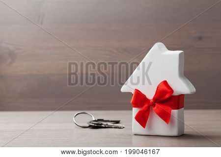 Small white house decorated red bow ribbon with bunch of keys on wooden background. Gift, real estate, purchase or buying a new home concept.