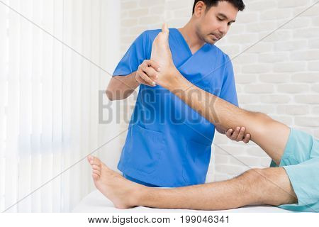 Therapist training rehab exercise to male patient in hospital - physical therapy concept
