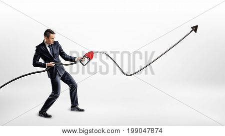 A businessman holds a gas pump nozzle which shots out oil into a black raising line with an upwards arrow. Growing oil market. Gas prices. Commodities business.