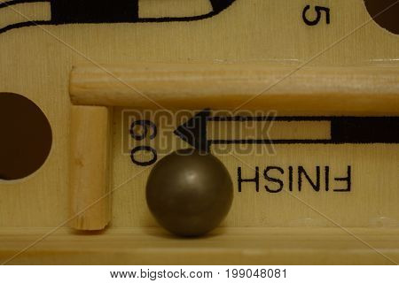 closeup of steel ball at the finish line of a labrynth