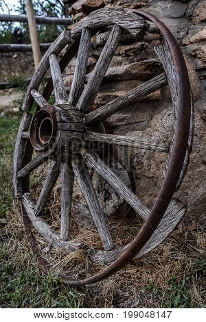 old covered wagon wheel in disrepair leaning against a wall of stone vertical