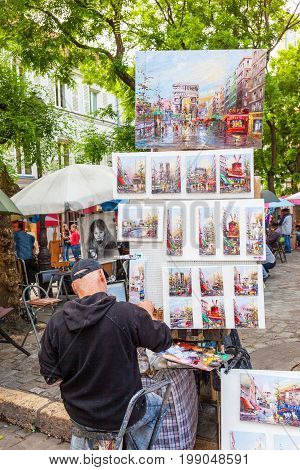 PARIS, FRANCE - JUNE 6, 2012: An unidentified Parisian artist painting at his outdoor stall in Montmartre in Paris.