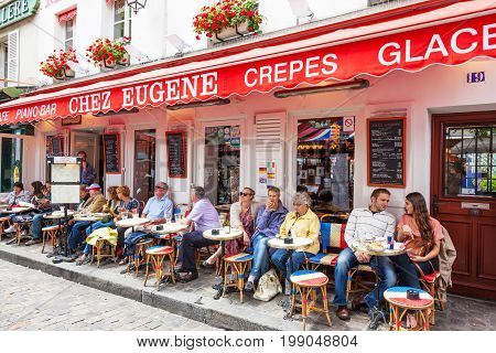 PARIS FRANCE - JUNE 6 2012: Unidentified patrons relaxing at a cafe in Montmartre in Paris.