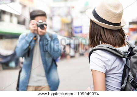 Traveling Asian couple tourist backpackers taking photo in Khao san road Bangkok Thailand on holidays