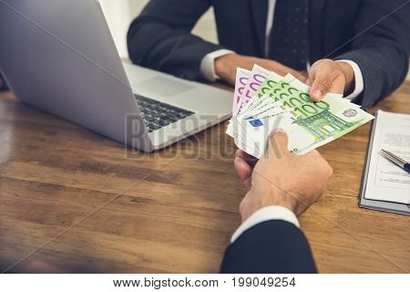 Businessman giving money Euro banknotes to his partner while making contract