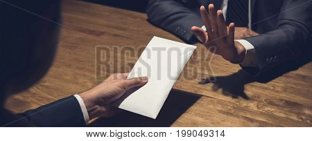Businessman rejecting money in white envelope offered by his partner in the dark anti bribery concept - panoramic banner