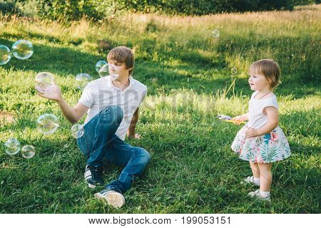 father plays with his daughter with soapbubble outside in the park