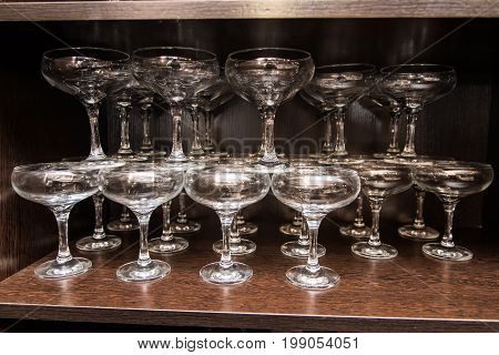 Clean glass glasses for drinks stand on the shelf